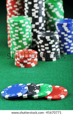 different color chips for gambling on green background.