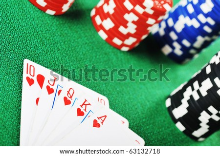 different color chips for gamblings and playing cards on green