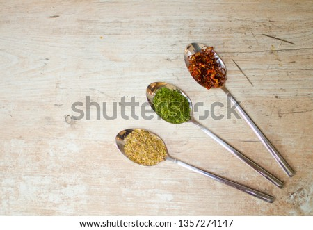 Different color dried herbs dried coriander, dried oregano and dried chilli rings on metal spoons on a wooden board