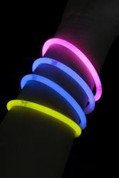 Different color glow stick bracelets on hand