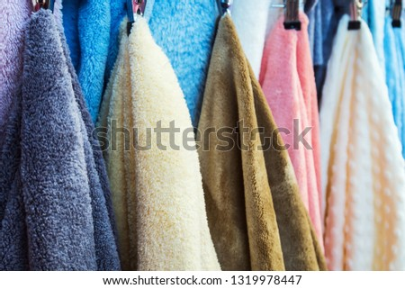 different color large bath towels on the hanger in the shower room, in the store or on the market