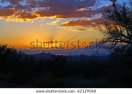 Different color rays of light streaking from sun which is behind a cloud during sunset over Saguaro National Park near Tucson, Arizona.
