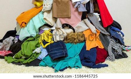 Different colored clothes background. Mixed up dresses, jeans, skirts and other used clothes Foto d'archivio ©