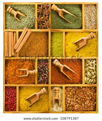 Different colored ground spices powders and solid with wooden spoons in a wooden box as a background