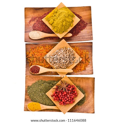 Different colored ground spices powders and solid with wooden spoons in a wooden coasters set in a pyramid isolated on white background