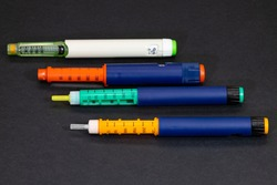 different colored insulin syringe pens for diabetes treatment on black background