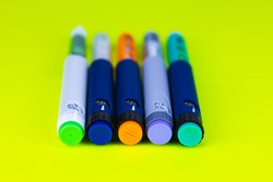 Different colored insulin syringe pens for insulin therapy on green background. Close-up, selective focus.