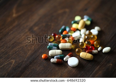 Different colored medications and tablets on a wooden texture table #648692320