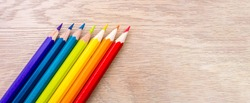 Different colored pencils photo with space for text. Seven pencils of rainbow colors lie on the table. Copyspace. Back to school. Wooden background.