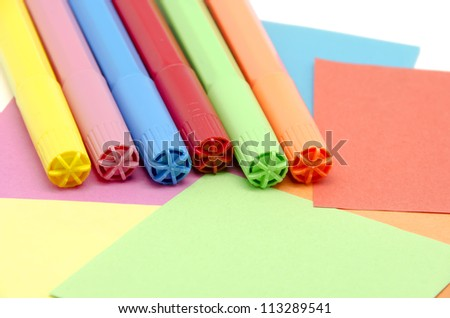 Different colored pens with colored paper