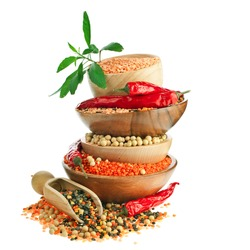 Different colorful lentils in a wooden bowl, soya beans, red chilli peppers with leaves