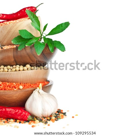 Different colorful lentils in a wooden bowl, soya beans, red chilli peppers with leaves and garlic - stock photo