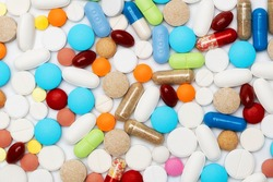 Different colorful medication and pills on white lab table. Creative health care of pharmaceutical concept. Close up of heap of capsules. Flat lay.