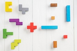 Different colorful shapes wooden blocks on beige background, flat lay. Geometric shapes in different colors, top view. Concept of creative, logical thinking or problem solving. Copy space.
