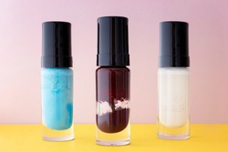 Different colors of aged and broken nail polish in selective focus. Old and dry nail varnish without labels. Hardened and dried finger nail polish bottles. PAO code and expired cosmetics concept.