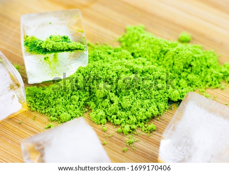 Different colors of Japanese matcha tea: green, red and blue with ice pieces on a wooden stand. Powder, acai berry powder from green tea leaves and powder of the flowers of the clitoris