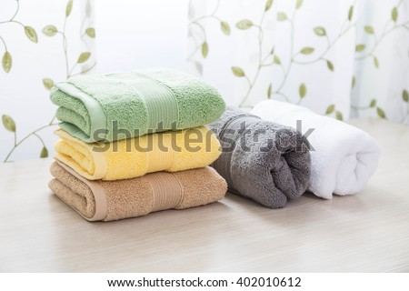 Different colors of towel in front of the cotton print curtain background