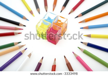 different coloured pencils and glass cubes filled with colourful liquid