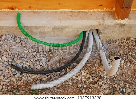 Different coloured plastic conduits coming out of the foundations of a newly built wood house. The conduits are for carrying various electrical cables. In Udine, Friuli-Venezia Giulia, Italy  Stock photo ©