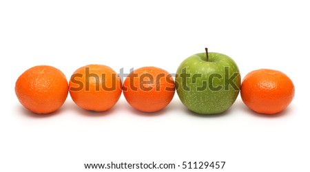 different concepts - green apple between mandarins