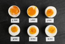 Different cooking time and readiness stages of boiled chicken eggs on black table, flat lay