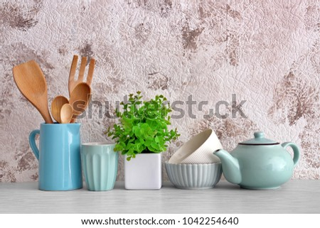 Different cooking utensils with dishware on table #1042254640