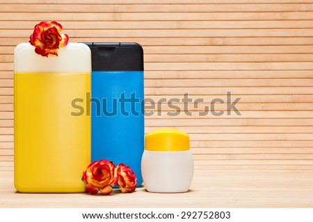Different cosmetic products for body care with flowers on wooden surface. Copy space