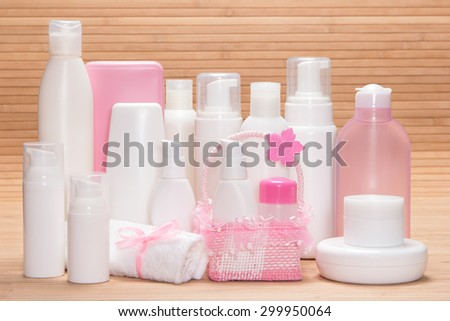 Different cosmetic products for skincare on wooden surface. Various facial cleansers, makeup removers, moisturizing and nourishing creams, cute wicker basket and towel tied with satin ribbon with bow