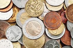 Different currency coins stacked. Pile of money. Metal coins texture. Financial world background. German one euro Eagle, twenty albanian leke coin.