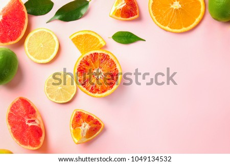 Different cut citrus fruits on color background, top view #1049134532