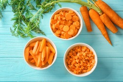 Different cuts of carrot in bowls on wooden background