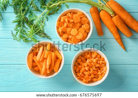 Different cuts of carrot in bowls on wooden background #676575697