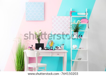 Different decorative cosmetics and accessories on table in room