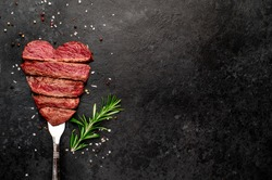 Different degrees of roasting beef steak in heart shape with spices on a meat fork on a stone background with a copy of the space for your text