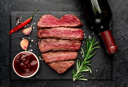 Different degrees of roasting heart-shaped beef steak with spices and bottle of wine on a stone background. valentines day celebration concept