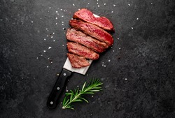 Different degrees of roasting heart shaped beef steak with spices on a meat knife on a stone background with copy space for your text