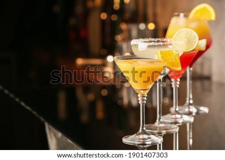 Different delicious cocktails on black table in bar. Space for text Stock foto ©