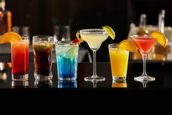 Different delicious cocktails on counter in bar