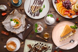 Different desserts with fruits and coffee, top view