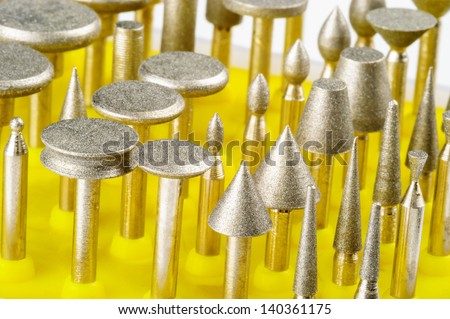 Different diamond coated drill bits in yellow rack.