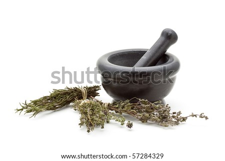 Different dried herbs in stone mortar over white background