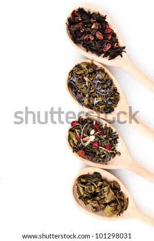 Different dry green and black tea in wooden spoons isolated on white