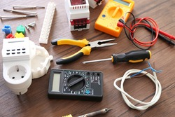 Different electrical tools on wooden table, top view