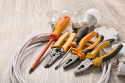 Different electrician's supplies on wooden floor