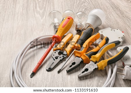 Different electrician's supplies on wooden floor Stock photo ©