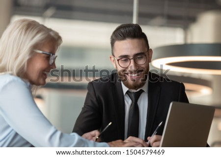 Different ethnicity and age colleagues sit at office desk work on project use pc, european manager consulting arabian client showing him on laptop offer process orders and provide information concept