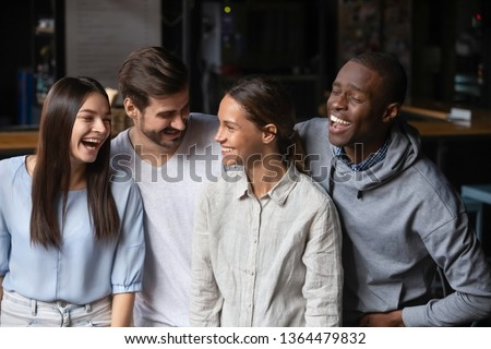 Different ethnicity millennial friends girls and guys standing in public place cafeteria laughing telling jokes people on the same wavelength having fun. Racial and ethnic equality, friendship concept
