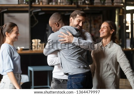 Different ethnicity multi racial guys hugging greeting each other best friends gathered in public place, spending Friday hanging out together, chance meeting, friendship between diverse people concept