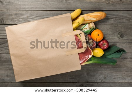 Different food in paper bag on wooden background, close up. Grocery shopping concept, top view