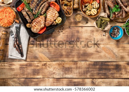 Different foods cooked on the grill on the wooden table with copy space, grilled steak, grilled sausage and grilled vegetables. Top view #578366002